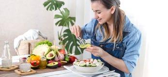 Mujer joven y feliz que come la ensalada en la tabla imágenes de archivo libres de regalías