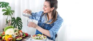 Mujer joven y feliz que come la ensalada en la tabla imagen de archivo libre de regalías