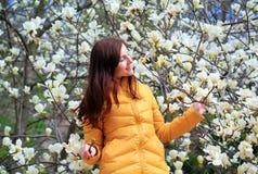 Mujer joven y floración del árbol de la magnolia Imagen de archivo libre de regalías