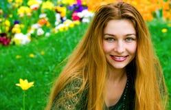 Mujer joven y flores en fondo Fotos de archivo