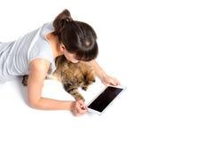 Mujer joven y gato usando la tableta en el fondo blanco Imagen de archivo