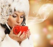 Mujer joven y hermosa con una taza roja en un fondo de la Navidad Fotos de archivo