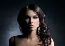 Mujer joven y hermosa en joyas sobre fondo oscuro fotos de archivo