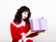 Mujer joven y hermosa en la capa roja que sostiene una caja agradable del regalo de Navidad Imagen de archivo