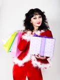 Mujer joven y hermosa en la capa roja que sostiene una caja agradable y los panieres del regalo de Navidad Fotos de archivo libres de regalías
