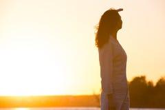 Mujer joven y hermosa en la mirada ligera de la puesta del sol lejos Imagen de archivo libre de regalías