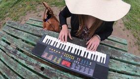 Mujer joven y hermosa que juega el sintetizador en la tabla de un parque, Francia almacen de metraje de vídeo