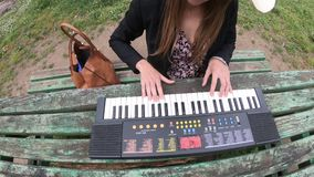 Mujer joven y hermosa que juega el sintetizador en la tabla de un parque, Francia metrajes