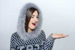 Mujer joven y hermosa que lleva a cabo un regalo de Navidad agradable emoción de la mano Imagen de archivo libre de regalías