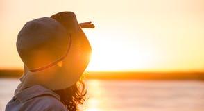 Mujer joven y hermosa que lleva un sombrero en la mirada ligera de la puesta del sol Fotografía de archivo