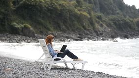 Mujer joven y hermosa que mecanografía en el ordenador portátil moderno cerca del mar almacen de video