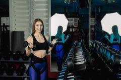 Mujer joven y hermosa que se resuelve con pesas de gimnasia en gimnasio Rizos del bíceps fotos de archivo libres de regalías