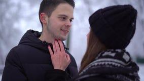 Mujer joven y hombre alto que miran en ojos de cada uno en ropa del invierno Cara de la caricia de la mujer del novio Pares felic almacen de metraje de vídeo