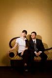 Mujer joven y hombre de negocios que se sientan en el sofá Fotos de archivo libres de regalías