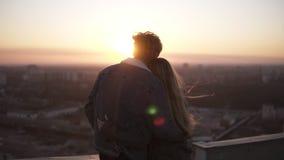 Mujer joven y hombre de pelo largo que miran la ciudad la puesta del sol que se coloca en el tejado del alto edificio observación almacen de metraje de vídeo