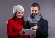 Mujer joven y hombre en abrigos de invierno con la tableta Imagen de archivo libre de regalías