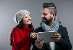 Mujer joven y hombre en abrigos de invierno con la tableta Fotografía de archivo libre de regalías