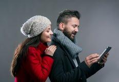Mujer joven y hombre en abrigos de invierno con la tableta Foto de archivo