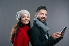 Mujer joven y hombre en abrigos de invierno con la tableta Fotos de archivo