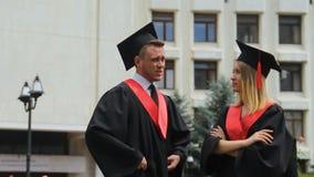 Mujer joven y hombre en capas y casquillos que discuten el futuro, día de graduación almacen de video