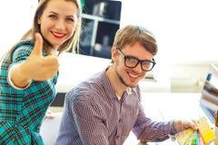 Mujer joven y hombre hermosos con el pulgar para arriba en oficina Fotos de archivo