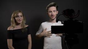 Mujer joven y hombre hermosos que hablan con la cámara y que presentan su competencia blogging video en medios sociales - metrajes