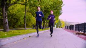 Mujer joven y hombre que corren en el parque Otoño metrajes