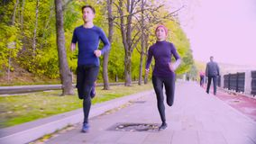 Mujer joven y hombre que corren en el parque Otoño almacen de metraje de vídeo