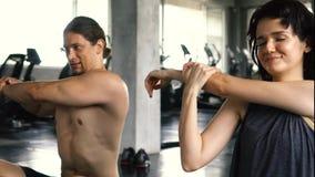 Mujer joven y hombre que estiran sus brazos en el piso del gimnasio Dos pares de las personas que se resuelven dentro almacen de video