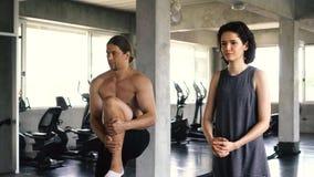 Mujer joven y hombre que estiran sus piernas en el piso del gimnasio Dos pares de las personas que se resuelven dentro metrajes
