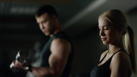 Mujer joven y hombre que hacen un entrenamiento de la aptitud con pesas de gimnasia