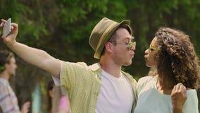 Mujer joven y hombre que se divierten, tomando selfies en el festival de música del verano almacen de metraje de vídeo