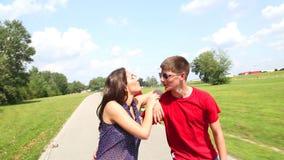 Mujer joven y hombre rollerblading en un día de verano soleado hermoso en el parque, abrazándose almacen de metraje de vídeo