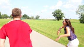 Mujer joven y hombre rollerblading en un día de verano soleado hermoso en el parque, bailando almacen de metraje de vídeo