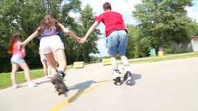 Mujer joven y hombre rollerblading en un día de verano soleado hermoso en el parque, llevando a cabo las manos almacen de metraje de vídeo