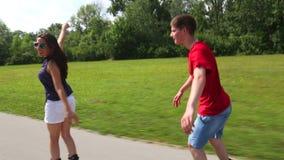 Mujer joven y hombre rollerblading en un día de verano soleado hermoso en el parque, sosteniendo la cintura almacen de metraje de vídeo