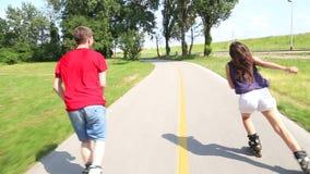 Mujer joven y hombre rollerblading en un día de verano soleado hermoso en parque, divirtiéndose metrajes