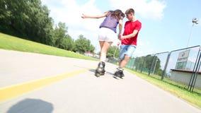 Mujer joven y hombre rollerblading en un día de verano soleado hermoso en parque, vista de piernas almacen de video