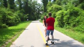 Mujer joven y hombre rollerblading en un día soleado en el parque, llevando a cabo las manos almacen de video