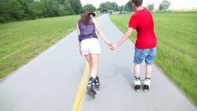 Mujer joven y hombre rollerblading y que se realizan en parque en un día caliente hermoso, llevando a cabo las manos metrajes