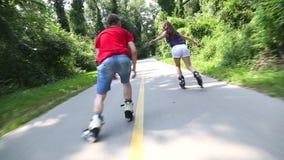 Mujer joven y hombre rollerblading y que se realizan en parque en un día caliente hermoso, yendo rápidamente almacen de video