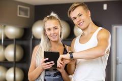 Mujer joven y hombre sonrientes con la tableta en el gimnasio de la aptitud Imagen de archivo libre de regalías