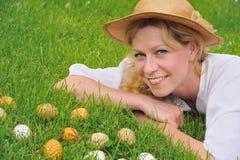 Mujer joven y huevos de Pascua en la hierba Imagenes de archivo