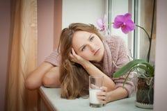 Mujer joven y leche. Fotografía de archivo libre de regalías