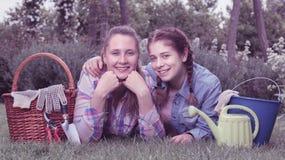 Mujer joven y muchacha sonrientes con las herramientas que cultivan un huerto adentro al aire libre Imagenes de archivo