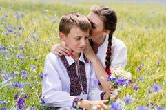 Mujer joven y muchacho en campos de trigo del verano Foto de archivo libre de regalías