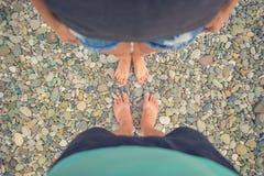 Mujer joven y muchacho que se colocan en piedras redondeadas de un guijarro Una muchacha y un muchacho que gozan de una playa inu Fotografía de archivo