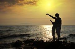 Mujer joven y muchacho que se colocan en roca en el mar Imagenes de archivo