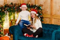 Mujer joven y muchacho sonrientes que se sientan en el sofá con el libro cerca de la chimenea de la Navidad fotografía de archivo