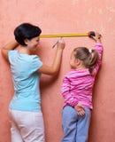 Mujer joven y niña con la cinta de medición imágenes de archivo libres de regalías